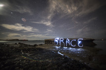 """Grace"" in neon lights on rocks in the ocean water."