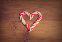 A heart made of peppermint sticks on a wooden table.