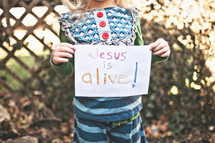 """girl holding a sign that says """"Jesus is Alive"""""""
