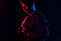 Red and blue light shining on a man who is adjusting his tie.