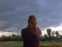 woman and an approaching storm