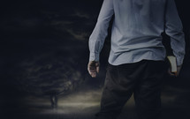 a man facing a storm holding a Bible