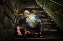 children sitting on steps holding the earth