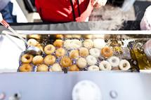 Donut frying in a vat of oil.