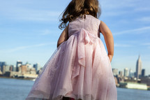 little girl in front of a city skyline