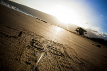 Jesus written in the sand on a beach at sunrise.