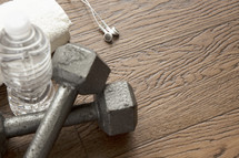 earbuds, barbells, fitness, bottled water, towel, wood floor