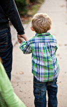 toddler boy walking holding his fathers hand