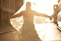bride holding her vail out in the sunlight