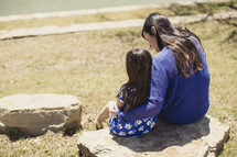 Mother embracing daughter while sitting on a rock in a park.