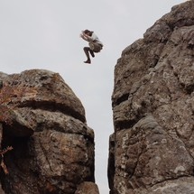 man leaping across a steep ravine