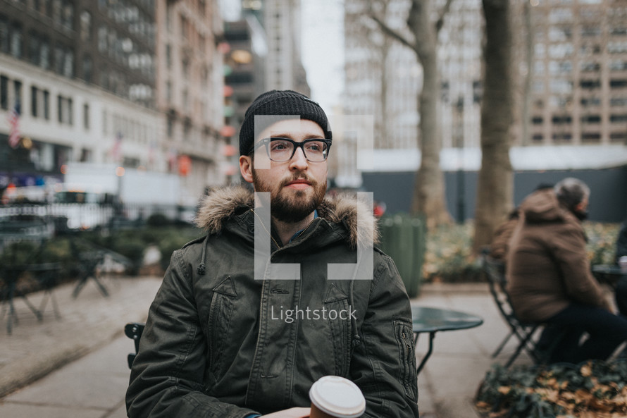 a man in a coat sitting in a city holding a coffee cup