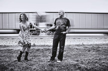 couple dancing in a field in front of train box cars