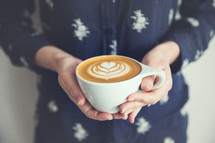 woman holding a cappuccino with a heart design.