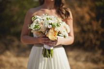 A bridesmaid holds a bouquet of flowers.