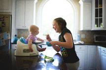 big sister feeding her infant sister baby food