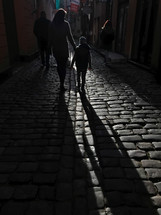 mother and son walking on a cobblestone street