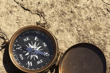 An open compass on bare earth.