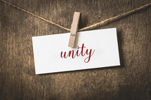 word unity on white card stock hanging from a clothespin on a clothesline