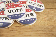 """Patriotic buttons reading, """"Vote,"""" and """"I Voted"""" on wood table."""