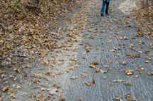 a man walking down a path in fall