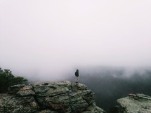 Man standing at the edge of a rocky cliff in the foggy haze.