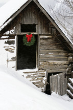 A Christmas wreath hanging on an old barn in the snow.