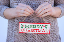 woman in a sweater holding a Merry Christmas sign
