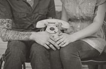a couple sitting holding a phone in their laps