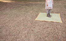 woman standing on a blanket in the grass