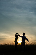 silhouettes of a couple dancing outdoors