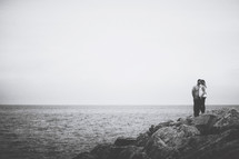 a couple standing on rocks on a shore kissing