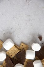 The ingredients for s'mores gathered at the bottom of a marble surface.
