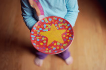 child holding a hand painted plate with a star