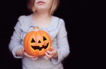 a child holding a jack-o-lantern