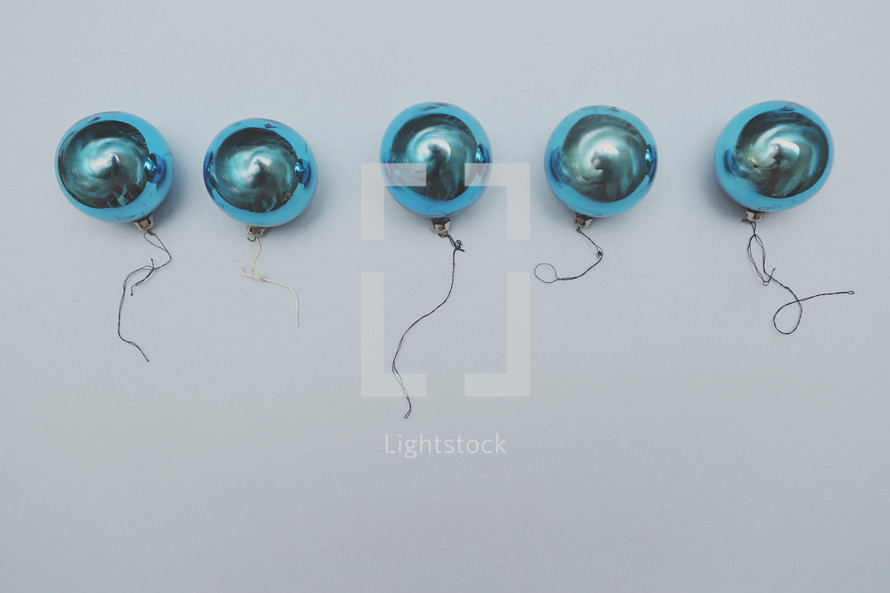 A row of shiny blue vintage ornaments with copy space.