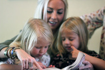 a mother reading to her daughters