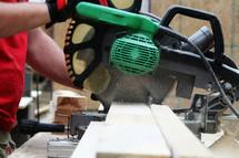 Man cutting a board with a miter saw.