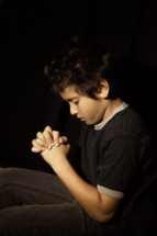 boy with his fingers laced in prayer