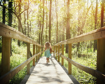 a little girl with a teddy bear running on a wood trail in the woods