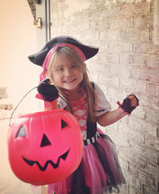 a little girl trick-or-treating dressed as a pirate