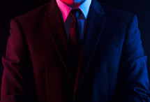 Red and blue light shining on a man in a suit and tie.