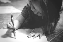 a toddler writing on paper with a pen
