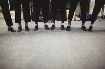 A group of men displaying their shoes and socks