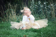 an infant girl in a tutu sitting in the grass covering her face