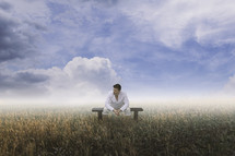a man sitting in a field under a blue sky