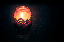 A candle burning in a decorative jar.