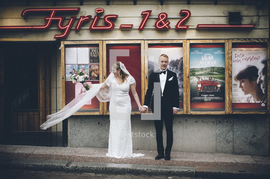 bride and groom in front of a vintage movie theater