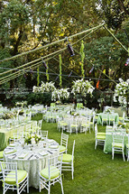empty set tables before a wedding reception green, forest event, dinner party chairs tables flatware plates
