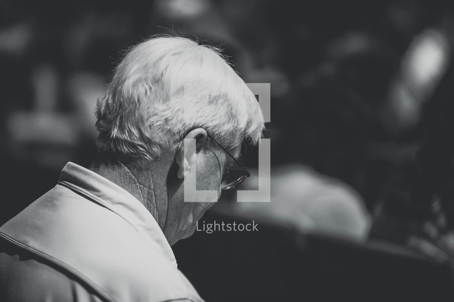 an elderly man in prayer at church